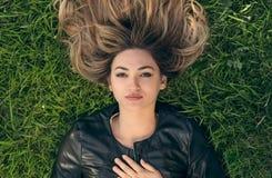 Mujer joven feliz que pone en la hierba en parque Imágenes de archivo libres de regalías