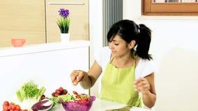Mujer joven feliz que prepara la ensalada en casa almacen de video