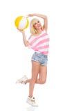 Mujer joven feliz que presenta con una pelota de playa Imagen de archivo