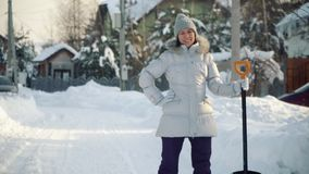 Mujer joven feliz que presenta en la cámara con la pala en suburbios en invierno metrajes