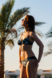 Mujer joven feliz que presenta en traje de baño del bikini sobre piscina y playa con el fondo de las palmeras Imagenes de archivo