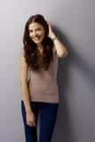 Mujer joven feliz que presenta por la pared gris Imagenes de archivo