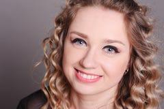 Mujer joven feliz que presenta sobre gris Fotos de archivo libres de regalías