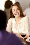 Mujer joven feliz que ríe en un restaurante Foto de archivo