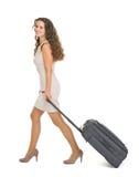 Mujer joven feliz que recorre con la maleta de las ruedas Imágenes de archivo libres de regalías