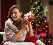 Mujer joven feliz que sacude la actual caja cerca del árbol de navidad Imagenes de archivo