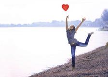 Mujer joven feliz que salta con un globo formado del corazón Foto de archivo libre de regalías