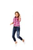 Mujer joven feliz que salta dando los pulgares para arriba Imagen de archivo libre de regalías