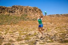 Mujer joven feliz que salta en la playa Foto de archivo libre de regalías