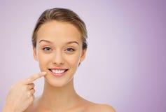Mujer joven feliz que señala el finger a su sonrisa Fotos de archivo
