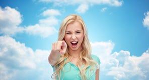 Mujer joven feliz que señala el finger a usted Fotos de archivo