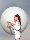 Mujer joven feliz que se coloca con el globo blanco foto de archivo