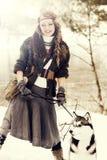 Mujer joven feliz que se coloca con el perro del husky siberiano Fotografía de archivo