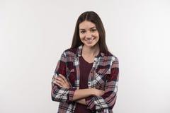 Mujer joven feliz que se coloca con sus brazos cruzados Imagen de archivo libre de regalías