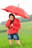 Mujer joven feliz que se coloca en la lluvia Fotos de archivo libres de regalías