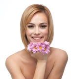 Mujer joven feliz que se reclina la barbilla en las flores Foto de archivo libre de regalías