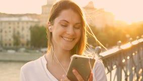 Mujer joven feliz que se relaja al aire libre Música que escucha de la muchacha hermosa en su smartphone Sol del verano que brill almacen de video
