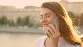 Mujer joven feliz que se relaja al aire libre Muchacha hermosa que habla en su smartphone Sol del verano que brilla metrajes