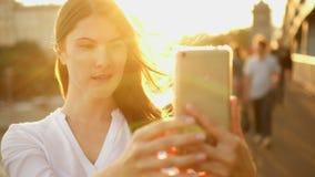 Mujer joven feliz que se relaja al aire libre Muchacha hermosa que hace el selfie en smartphone Sol del verano que brilla metrajes