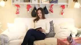 Mujer joven feliz que se relaja en el libro de lectura del sofá almacen de video