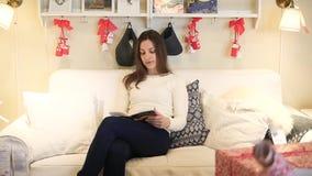 Mujer joven feliz que se relaja en el libro de lectura del sofá almacen de metraje de vídeo