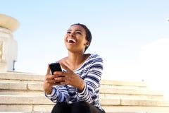 Mujer joven feliz que se sienta afuera usando el teléfono móvil Imagen de archivo