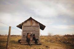 Mujer joven feliz que se sienta con su perro negro en fron de la casa de madera vieja fotos de archivo