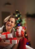 Mujer joven feliz que se sienta delante del árbol de navidad con los regalos Fotografía de archivo libre de regalías