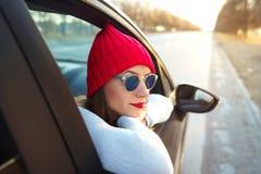 Mujer joven feliz que se sienta en asiento de pasajero del coche y que mira hacia fuera Imagenes de archivo