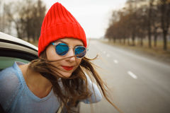 Mujer joven feliz que se sienta en asiento de pasajero del coche y que mira hacia fuera Fotografía de archivo libre de regalías