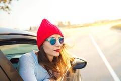 Mujer joven feliz que se sienta en asiento de pasajero del coche y que mira hacia fuera Foto de archivo