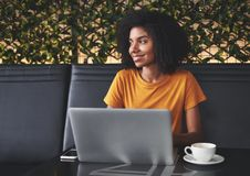 Mujer joven feliz que se sienta en café con el ordenador portátil en la tabla fotografía de archivo
