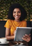 Mujer joven feliz que se sienta en café usando la tableta digital imágenes de archivo libres de regalías