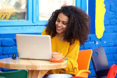 Mujer joven feliz que se sienta en el café al aire libre usando el ordenador portátil foto de archivo