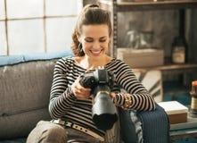 Mujer joven feliz que se sienta en el diván y que usa el dslr imagen de archivo libre de regalías