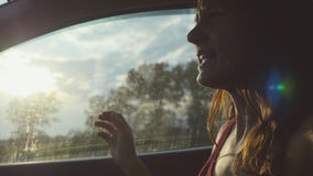 Mujer joven feliz que se sienta en el pasajero del coche que mira hacia fuera la ventana el día soleado que disfruta de paseo rur Imagen de archivo libre de regalías