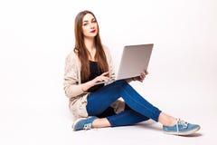 Mujer joven feliz que se sienta en el piso con las piernas cruzadas y que usa el ordenador portátil Fotografía de archivo