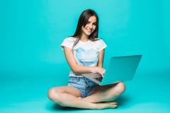 Mujer joven feliz que se sienta en el piso con las piernas cruzadas y que usa el ordenador portátil en fondo del color Fotos de archivo libres de regalías
