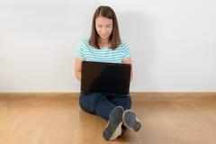 Mujer joven feliz que se sienta en el piso con las piernas y usi cruzados Fotografía de archivo