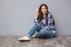 Mujer joven feliz que se sienta en el suelo Foto de archivo libre de regalías