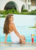 Mujer joven feliz que se sienta en la piscina con el cóctel Foto de archivo libre de regalías