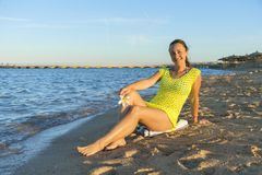 Mujer joven feliz que se sienta en la playa mujer que se sienta en la playa arenosa contra el cielo azul al aire libre Una mujer  imagen de archivo