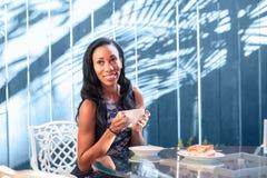 Mujer joven feliz que se sienta en la tabla en el café al aire libre Imagen de archivo libre de regalías