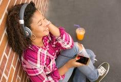 Mujer joven feliz que se sienta en la tierra que escucha la música Fotos de archivo
