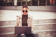 Mujer joven feliz que se sienta en las escaleras afuera y los trabajos sobre un l Fotografía de archivo