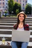 Mujer joven feliz que se sienta en las escaleras de la ciudad y que usa el ordenador portátil Imágenes de archivo libres de regalías