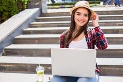 mujer joven feliz que se sienta en las escaleras de la ciudad y que usa el ordenador portátil Imagen de archivo libre de regalías