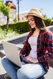 mujer joven feliz que se sienta en las escaleras de la ciudad y que usa el ordenador portátil Foto de archivo