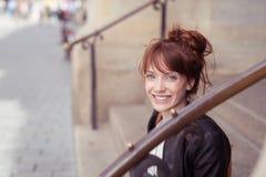 Mujer joven feliz que se sienta en pasos Fotos de archivo