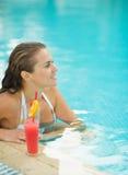 Mujer joven feliz que se sienta en piscina con el cóctel Foto de archivo libre de regalías